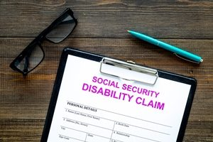 Social security disability claim in Idaho Falls with eyeglasses and pen.