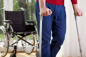 Twin falls personal injury lawyers - man on crutches with wheelchair in background